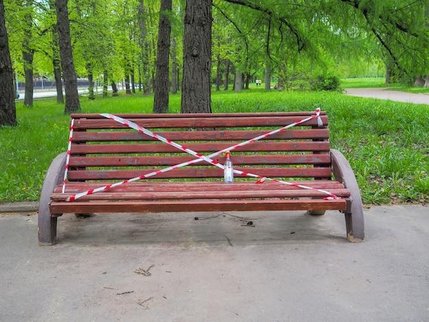 Скамейка в городском парке оклеена красно-белой сигнальной лентой безопасности.