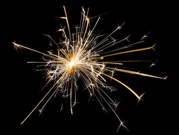 ベンガルの火が燃える。黒の孤立した背景にベンガルの火から火花。オーバーレイモードで画像を挿入するには_