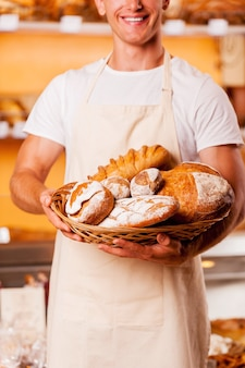 Лучшая выпечка в городе. обрезанное изображение молодого человека в фартуке, держащего корзину с выпечкой и улыбающегося, стоя в пекарне