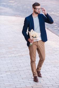 彼女にとって最高の花。花の花束を保持し、通りを歩いている間彼の眼鏡を調整するスマートカジュアルウェアのハンサムな若い男の全長