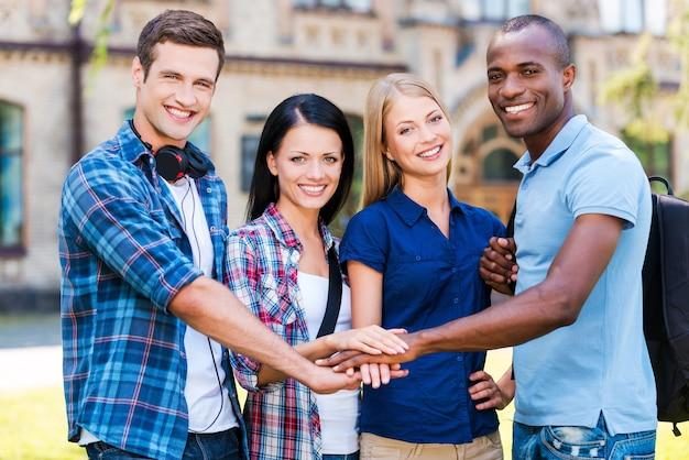 史上最高の友達。手をつないで、屋外に立って笑っている4人の幸せな若者