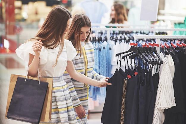 Лучшие друзья вместе проводят время. две красивые девушки делают покупки в магазине одежды. они одеты в одинаковую одежду
