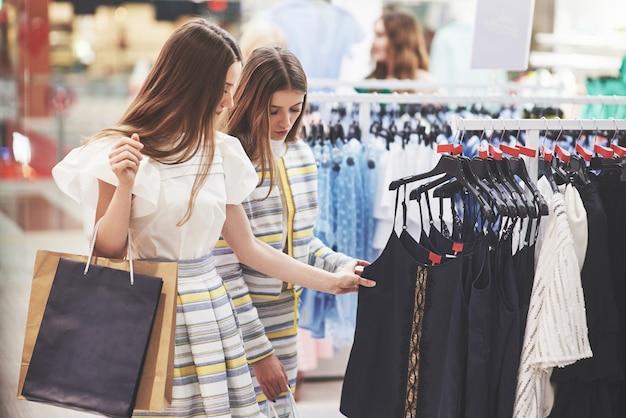 Лучшие друзья вместе проводят время. две красивые девушки делают покупки в магазине одежды. они были одеты в одинаковую одежду.