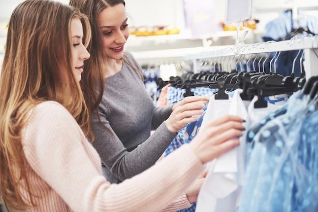 親友は一緒に時間を過ごします。 2人の美しい女の子が衣料品店で買い物をします。彼らは同じ服を着ていた。