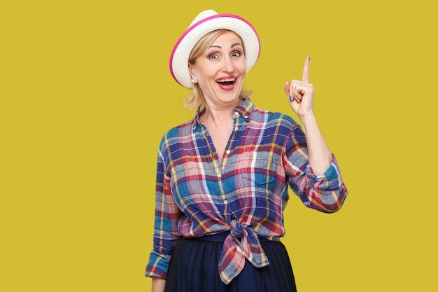 最高のアイデア。帽子を立てて、良い計画でカメラを見て驚いたカジュアルなスタイルで興奮した幸せなモダンでスタイリッシュな成熟した女性の肖像画。黄色の背景に分離された屋内スタジオショット。