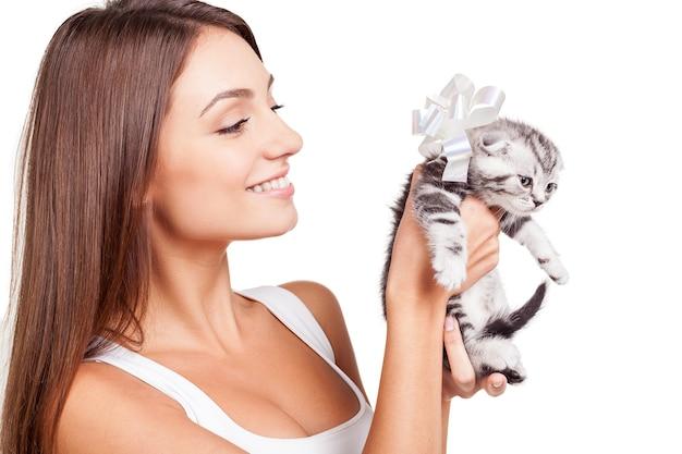 Лучший подарок. красивая молодая женщина держит маленького котенка с лентой на шее и улыбается, стоя на белом фоне