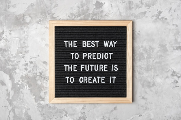 未来を予測する最良の方法はそれを作成することです。灰色の背景に黒い文字板の動機付けの引用。その日のコンセプトの心に強く訴える引用。グリーティングカード、はがき。