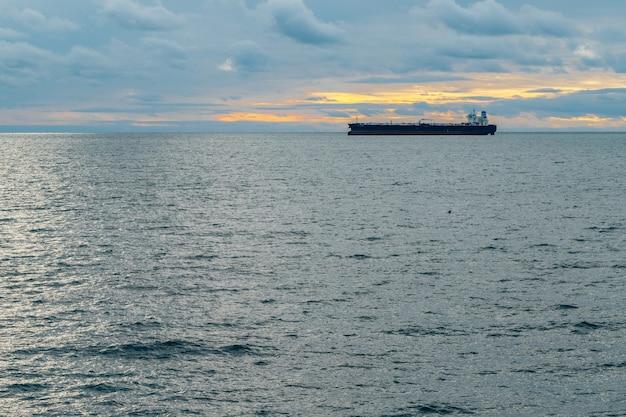 큰 화물선은 아름다운 흐린 하늘을 배경으로 바다를 항해합니다.