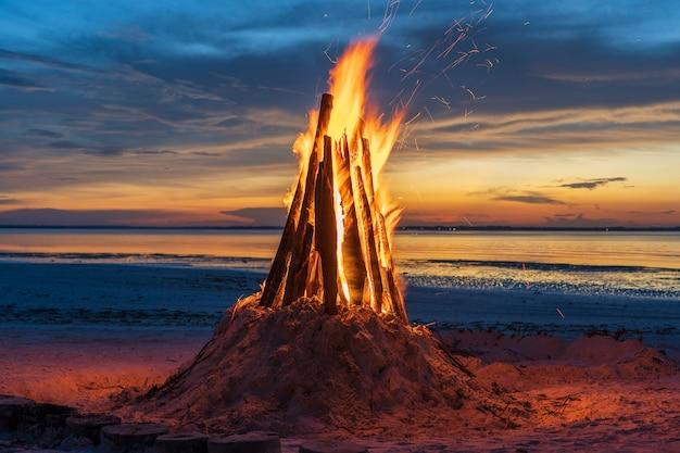 Большой пожар горит на фоне ночного неба у моря на острове занзибар, танзания, восточная африка, крупным планом. яркое пламя. вечерний костер.