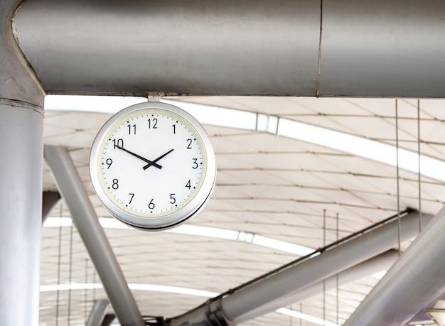 Большие настенные часы в метро для пассажиров, которые смотрят время на платформе метро.