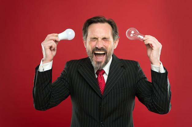 新しいアイデアの誕生。電気とエネルギー。スーツを着たビジネスマンは電球を保持します。あごひげを生やした男がインスピレーションを求めています。ランプ。ランプを持つ成熟したひげを生やした男。節電。男性を叫ぶ。仕事。