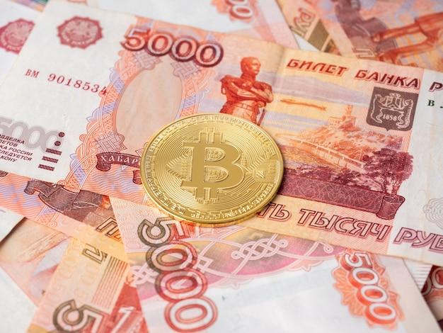 비트코인 동전은 러시아 루블의 배경에 놓여 있습니다. cryptocurrency 마이닝 및 마이닝 개념