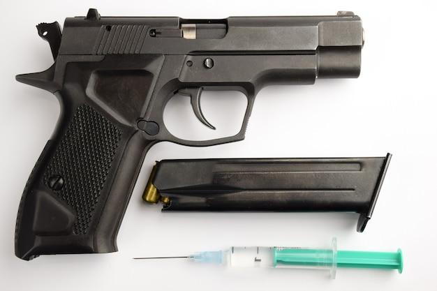 검은색 총은 클립과 흰색 배경에 바늘이 달린 플라스틱 주사기와 함께 놓여 있습니다