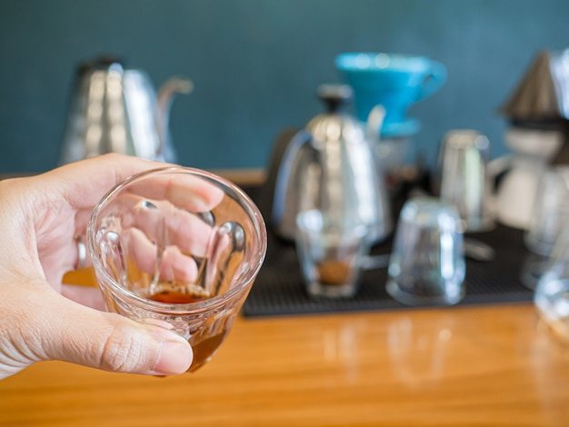 Черный горячий кофе извлекается путем капельного процесса в стакане эспрессо, который держит в руке мужчина.