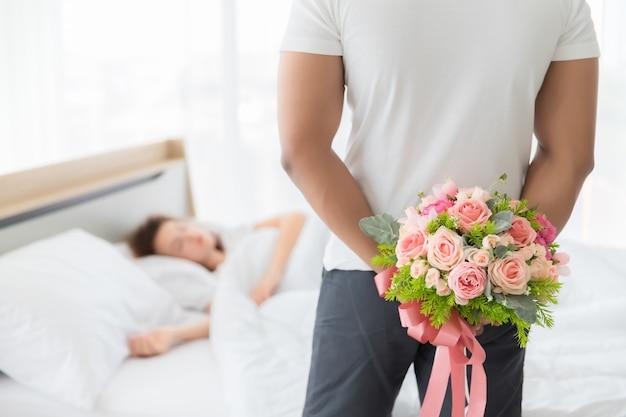 흑인은 편안한 옷을 입고 그의 손 뒤에 서서 분홍색 장미를 들고 있었다.