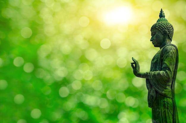 ブラックメタルの仏像は、自然の緑の背景の上に立っています。