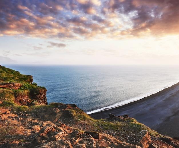 Черный песчаный пляж и горы рейнисфьяра от мыса на закате в исландии
