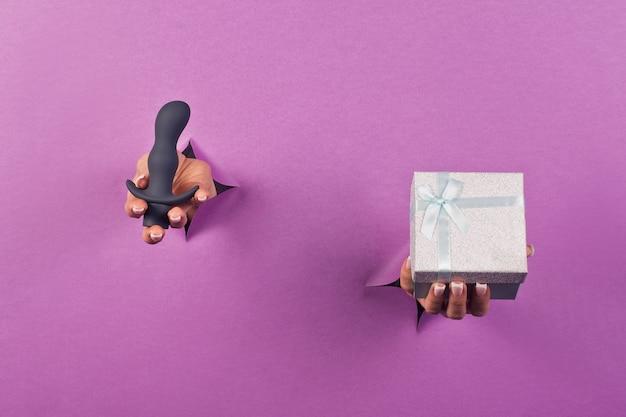 Черная силиконовая секс-игрушка на розовом фоне в женских руках