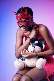 Черная женщина в маске бдсм-кошки смеется в наручниках с плюшевым мишкой в руках
