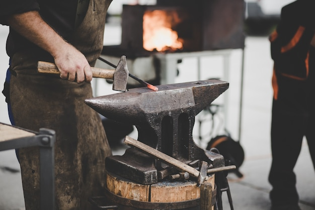 Кузнец вручную выковывает расплавленный металл на наковальне в кузнице.