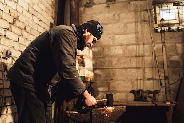 鍛冶屋は、金床の真っ赤な金属を手作業で鍛造し、火花を飛ばします。