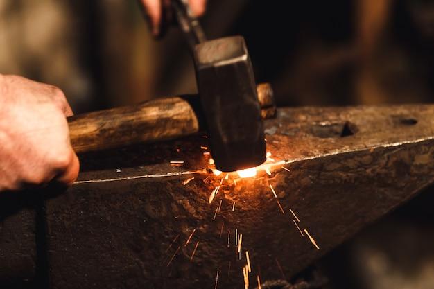 대장장이는 불꽃 놀이로 대장간에서 모루에 붉은 뜨거운 금속을 수동으로 단조합니다.