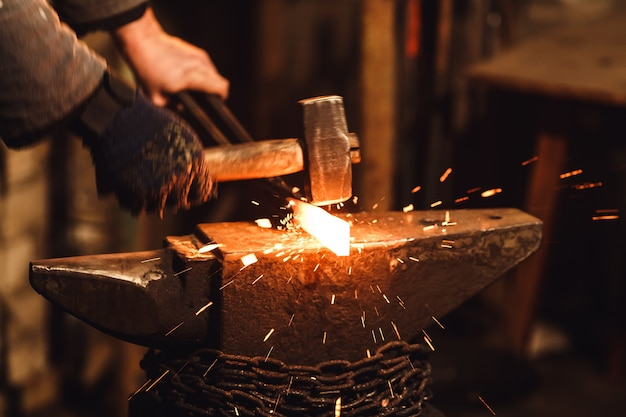 Кузнец вручную выковывает раскаленный металл на наковальне в кузнице искровым фейерверком.
