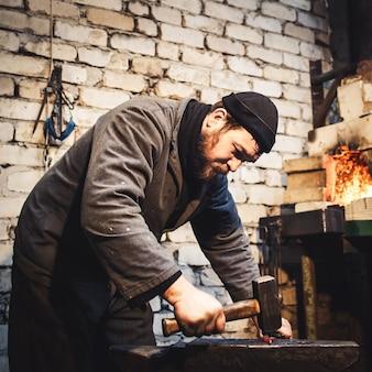 鍛冶屋はアンビルの真っ赤な金属を手作業で鍛造します。