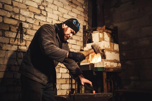 鍛冶屋はアンビルの真っ赤な金属を手作業で鍛造します