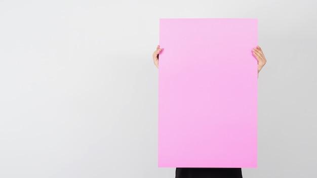 Пустая бумага розового цвета в руке человека на белом фоне.
