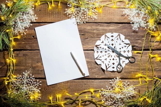 ペンとクリスマスの装飾が施された木製のテーブルの上の白紙。