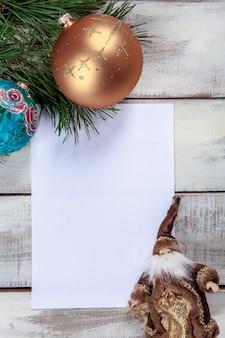 クリスマスの装飾と木製のテーブルの用紙の空白のシート。