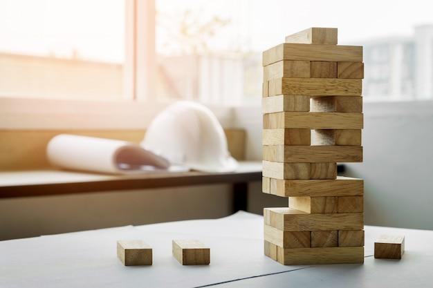 Блок деревянная башня игра с архитектурными инженерными планами или синими гравюрами компасы, карандаши и линейка на деревянном столе, концепция плана и строительства
