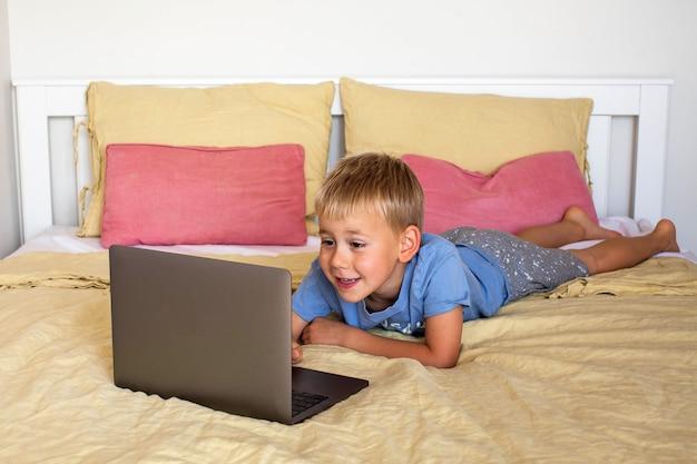 Светловолосый мальчик эмоционально общается через ноутбук по видеосвязи