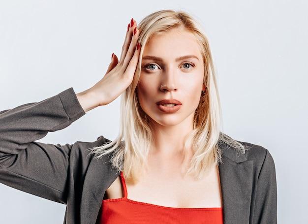 금발 소녀는 중요한 정보를 기억하고 이해했으며 머리에 손을 댄다. 여자는 사업의 선택을 의심하고 제안합니다. 광고에 대 한 격리 된 회색 배경입니다.