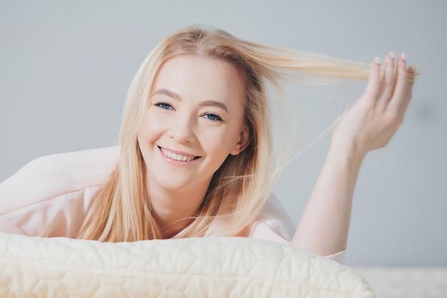 Блондинка в розовом лежит на полу. девушка улыбается. красота и здоровье лица, волос и кожи. копировать пространство