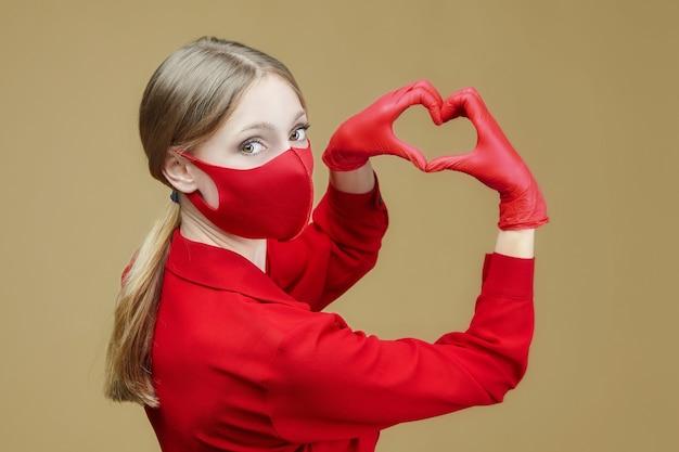赤い手袋とマスクを身に着けた金髪は、ハートの形に手を組んだ。コロナウイルスの予防の概念19。