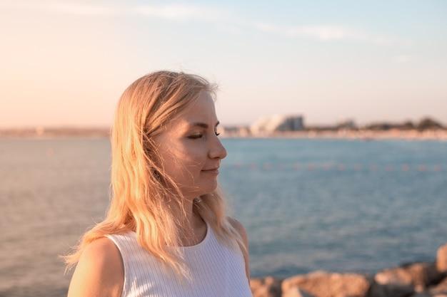 Блондинка на берегу моря на закате закрыла глаза сбоку портрет крупным планом летние каникулы на берегу моря