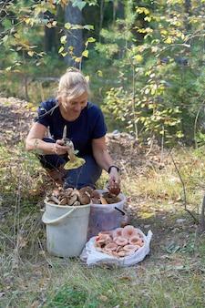 金髪は集められたキノコの前の森に座っています。女性は大きなポルチーニを手に持っています。縦ショット