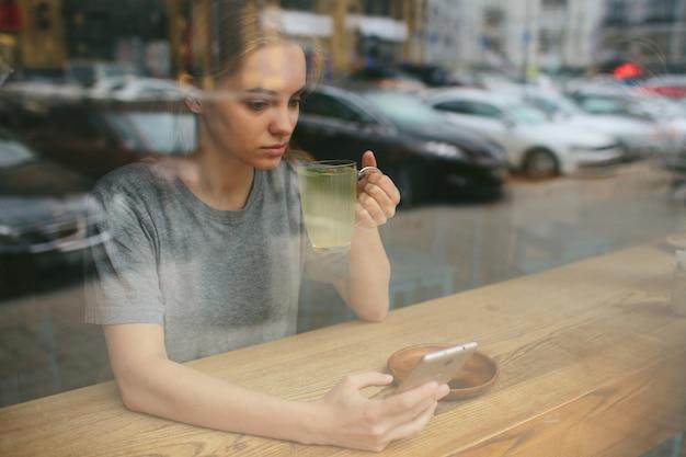 Блондинка пользуется телефоном. девушка и смартфон. женщина сидит в кафе с сотовым.