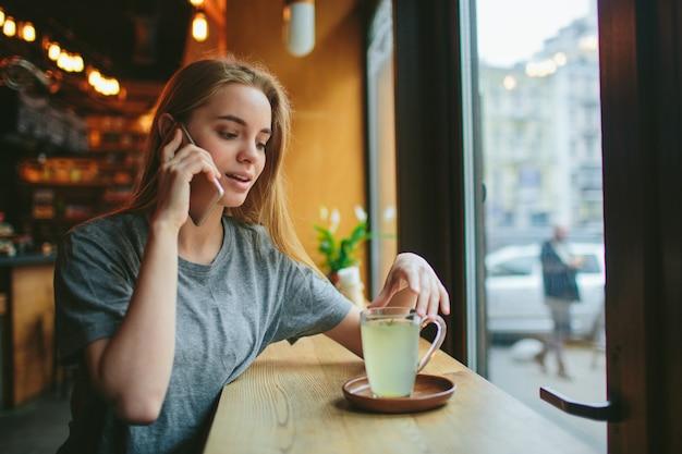 金髪は電話を使います。女の子とスマートフォン。セルラーを持ったカフェに女性が座っている。