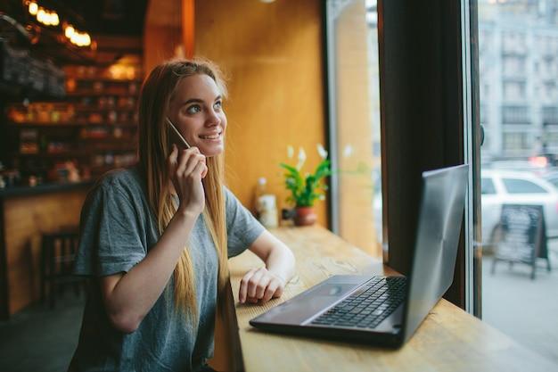금발은 전화를 사용합니다. 소녀와 스마트 폰. 여자는 휴대 전화와 함께 카페에 앉아있다