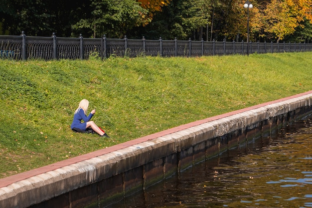 金髪の女性は川のほとりに一人で座っています。