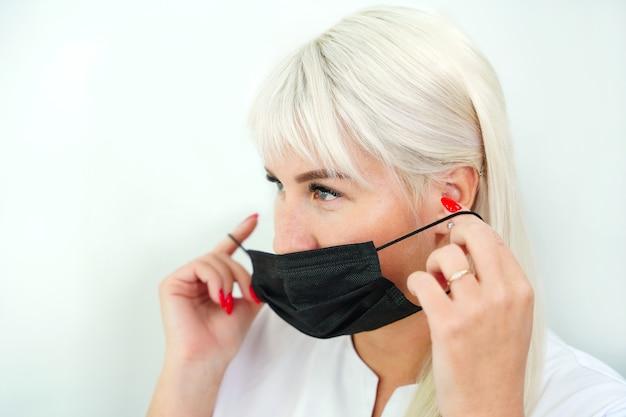 Блондинка надевает черную защитную маску на лицо на белом фоне защиты от коронавируса ...
