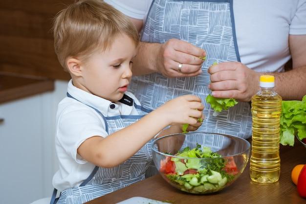 Blondehaired 아들과 아버지는 파란색 앞치마를 입고 주방에서 함께 다채로운 신선한 야채 샐러드를 준비합니다.
