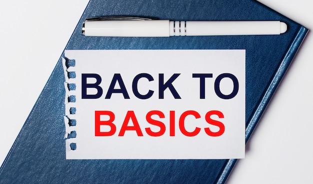 青い日記は明るい背景にあります。オンには、白いペンと1枚の紙があり、「基本に戻る」というテキストが付いています。