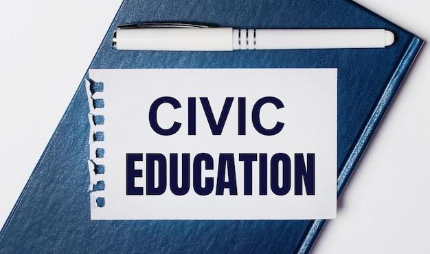 青い日記は明るい背景にあります。 onには、白いペンとciviceducationというテキストが書かれた紙があります。