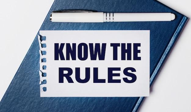 Синий дневник лежит на светлом фоне. у него есть белая ручка и листок бумаги с текстом знайте правила.