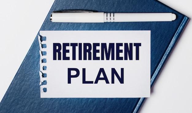 青い日記は明るい背景にあります。オンには、白いペンと「退職年金」というテキストが書かれた紙があります。