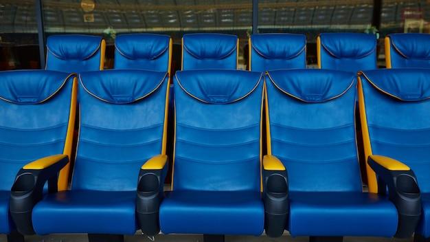 スポーツスタジアムの青い空の椅子。
